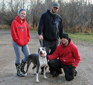 2 men and 1 female with a dog