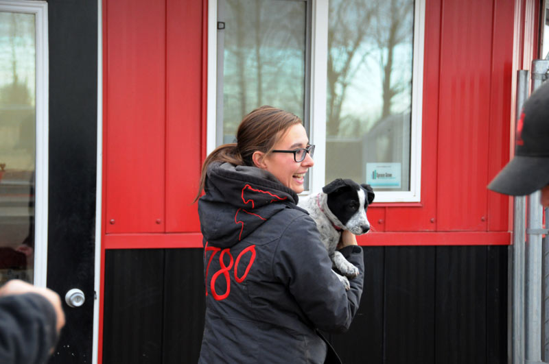 Staff carrying Blue Heeler puppy outside 780 facilities.